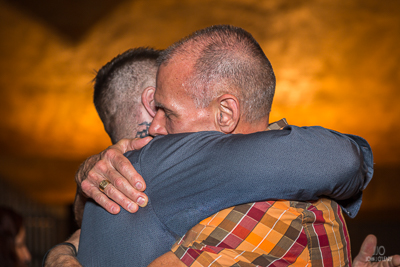 Pastor hugging a young man in the love of Christ.